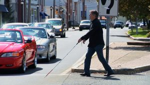 A blind man crossing the street with help of a stick unaware of the traffic on the street