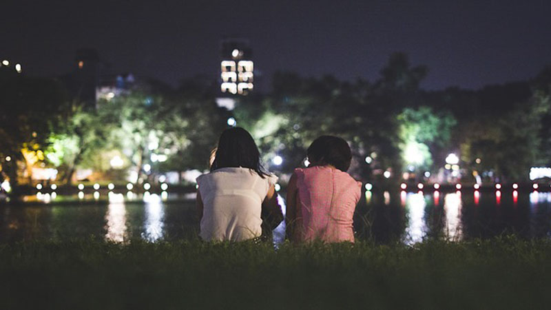 A girl and a boy communicating by the lake side at night time.