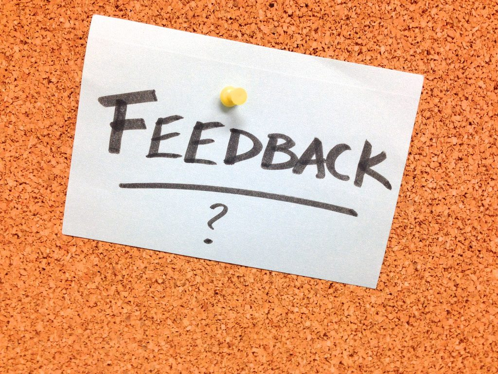 "A paper with the word ""FEEDBACK"" is pinned up on a brown board."