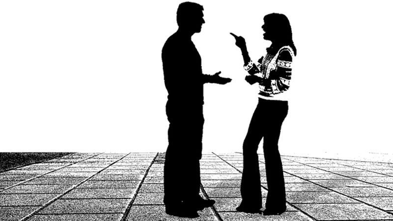 A woman laughing and pointing out her finger while talking to a man.