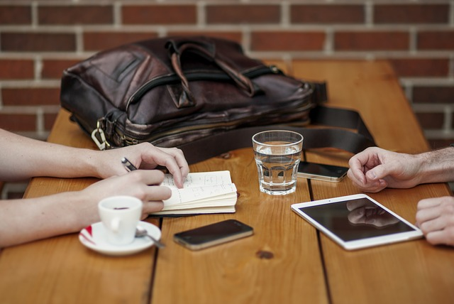 On a wooden table, there is a glass of water, a cup of tea, a leather bag, a mobile, a notepad and a notebook.