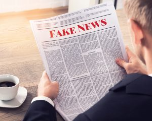 An overshoulder view of newspaper with Fake News written on it