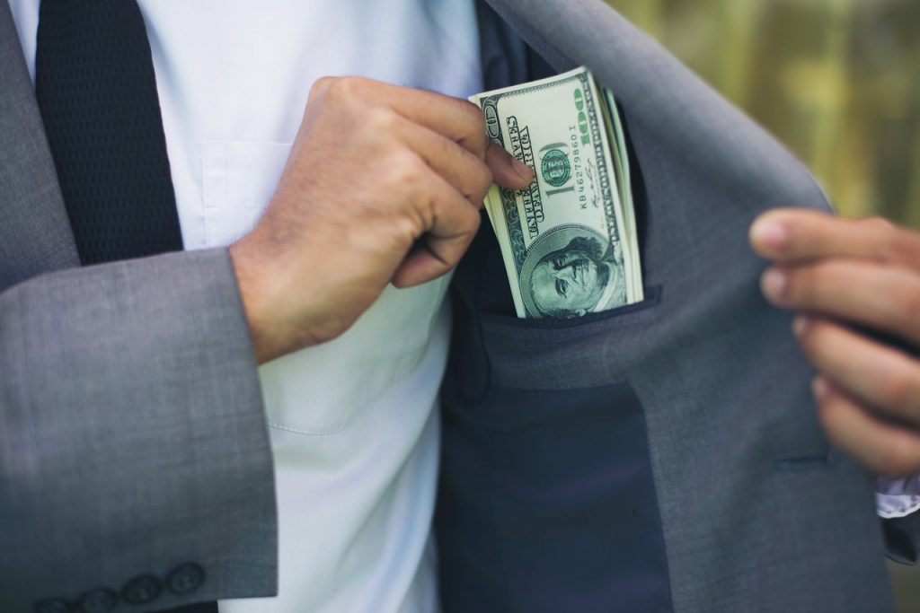 A man slipping cash into his coat pocket